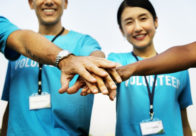 a group of volunteers with hands in