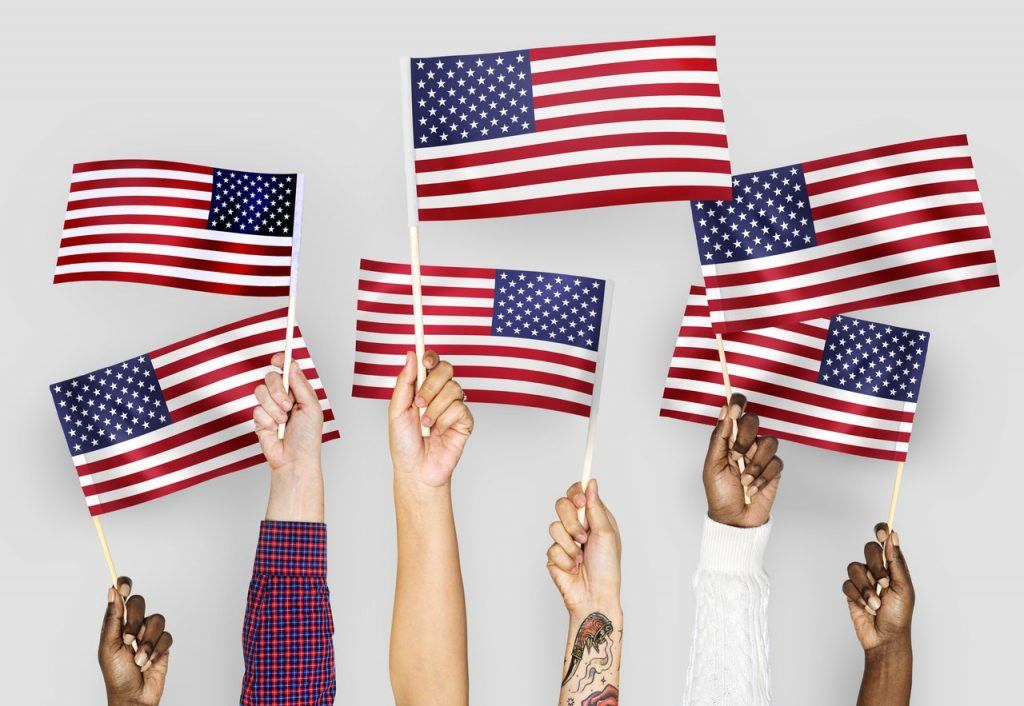 hands of all skin types holding small american flags